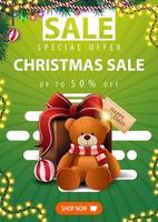 speciale aanbieding, kerstuitverkoop, tot 50 korting, groene verticale banner met kerstboomtakken, slingers, knop en cadeau met teddybeer vector