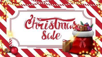kerstuitverkoop, kortingsbanner met rood en wit gestreepte textuur op de achtergrond en kerstman tas met cadeautjes