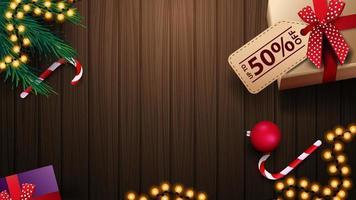 cadeau met labelprijs, zuurstok, kerstboomtak, kerstbal en slinger op houten tafel, bovenaanzicht. achtergrond voor kortingsbanners