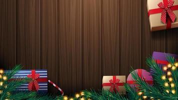kerstcadeautjes, kerstboomtak en gele slinger op houten tafel, bovenaanzicht. houten kerst achtergrond voor kortingsbanner of wenskaart