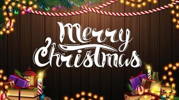 vrolijk kerstfeest briefkaart met slinger, kerstboomtak, boeken en kaars op een houten achtergrond