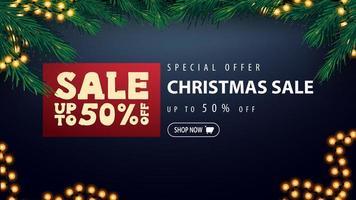 speciale aanbieding, kerstuitverkoop, tot 50 korting, blauwe kortingsbanner met rode prijskaartje, slinger en frame van kerstboomtakken