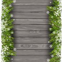 Kerstboomtakken op houten achtergrond vector