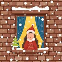 kerst meisje kijkt uit het raam