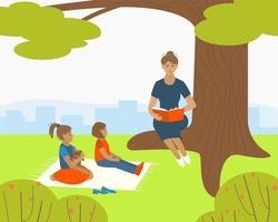 moeder of oppas leest een boek voor kinderen in het park