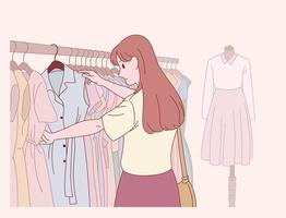 een vrouw kiest kleren in een kledingwinkel. vector