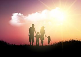 Silhouet van een familie die tegen een zonsonderganghemel loopt