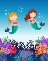 Twee zeemeerminnen zwemmen onder de oceaan