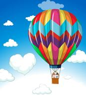 Kleurrijke ballon die in blauwe hemel vliegt