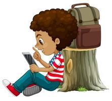 Een Afrikaanse jongen die tablet gebruikt