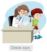 Een jongen die oren controleert met dokter