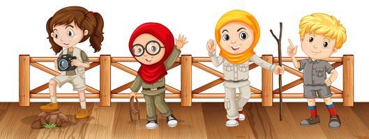 Vier kinderen in safari-outfit op de brug vector