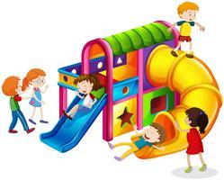 Kinderen die op dia spelen bij speelplaats