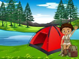 Een jongen die in bos kampeert vector