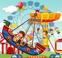 Kinderen rijden op attracties op de kermis