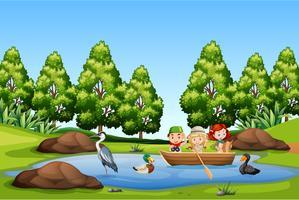 Kinderen peddelen boot in het meer