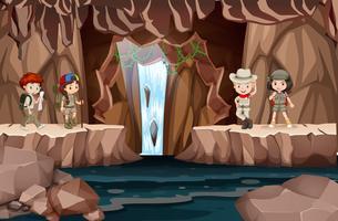 Kinderen die een grot met waterval verkennen