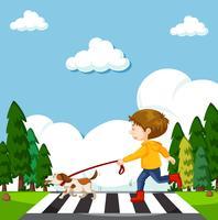 Een jongen die straat met hond oversteken