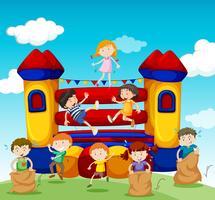 Kinderen spelen in het stuiterende huis vector
