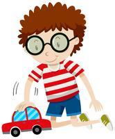 Weinig jongen die met stuk speelgoed auto speelt