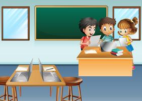 Drie kinderen werken op de computer in de klas