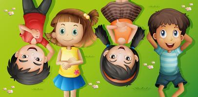 Vier kinderen liggen op gras vector