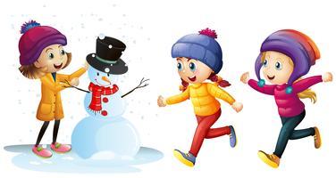 Drie meisjes die met sneeuwman spelen