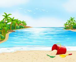 Uitzicht op de oceaan met emmer op het zand vector