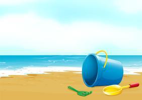 Een emmer, een vork en een schop op het strand