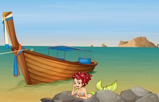 Een zeemeermin aan zee bij de houten boot