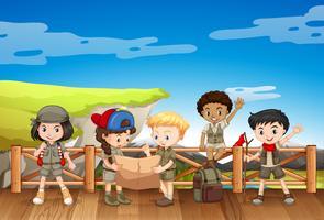 Vijf kinderen in safariuitrusting die zich op de brug bevinden