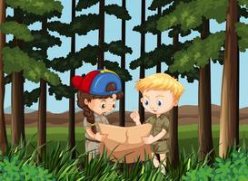 Jongen en meisjeslezingskaart in het bos
