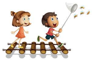 Twee kinderen vangen honingbij met net