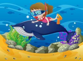 Meisje met walvis duiken onder de zee