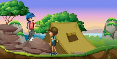 Twee kinderen kamperen aan het meer vector