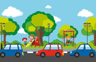 Scène met kinderen in speelplaats en auto's op de weg