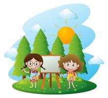 Twee meisjes die op canvas in tuin schilderen