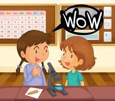 Twee meisjes die microscoop in klaslokaal bekijken