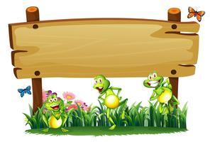 Een leeg houten bord in de tuin met speelse kikkers