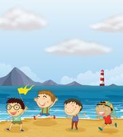 Vier jongens die op het strand spelen