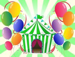 Een groene circustent in het midden van de kleurrijke ballonnen
