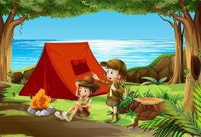Jongen en meisjesverkenner die in aard kamperen