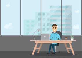 lachende zakenman zit en werkt op een laptopcomputer in zijn kantoor