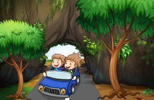 Een meisje en een jongen rijden in een auto langs de grot
