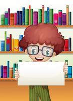 Een jongen die een leeg karton houdt dat zich voor de boekenplanken bevindt vector