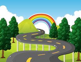 Parkscène met weg en regenboog op achtergrond