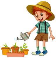 Een jongen die de planten water geeft