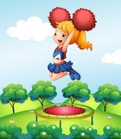 Een cheerdancer die haar rode pompons boven de trampoline houdt