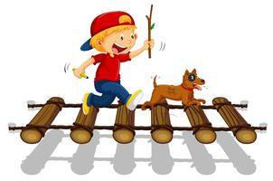 Jongen en hond die op de brug lopen
