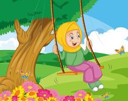 Een moslimmeisje zit op schommeling bij de tuin